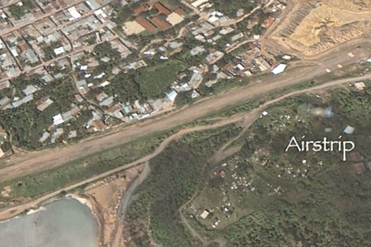 Airstrip is above reservoir adjacent to town.